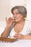 Senior woman eats chocolate candies Royalty Free Stock Photo