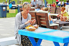 Senior woman eats street food Stock Image