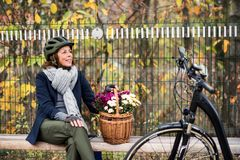 A senior woman with electrobike and flowers sitting on a bench outdoors in town. stock photo