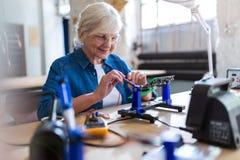 Senior woman in electronics workshop. Confident senior woman working in workshop stock image