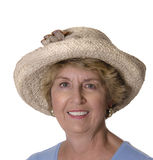 Senior woman in elegant straw hat. Studio shot on pure white background of a smiling senior woman dressed up in an attractive straw hat royalty free stock photos