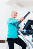Senior woman on elliptical trainer exercising Royalty Free Stock Photography