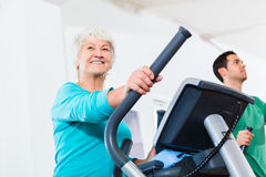 Senior woman on elliptical trainer exercising Stock Image
