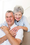 Senior woman embracing husband in house Stock Photography