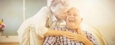 Senior woman embracing and kissing man. Senior women embracing and kissing men at home royalty free stock photography