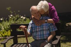 Senior woman embracing and kissing senior man in garden. Front view of romantic senior women embracing and kissing happy senior men in garden on sunny day royalty free stock photography