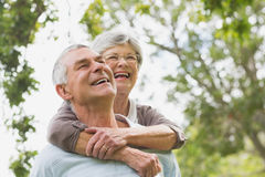 Senior woman embracing man from behind Royalty Free Stock Image