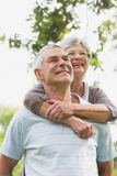 Senior woman embracing man from behind Stock Photo