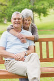 Senior woman embracing man from behind at park Stock Image
