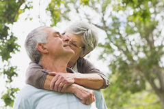 Senior woman embracing man from behind at park Stock Photography