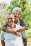 Senior woman embracing man from behind at park Royalty Free Stock Images