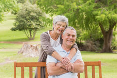 Senior woman embracing man from behind at park Royalty Free Stock Image