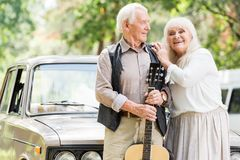 senior woman embracing man with guitar against beige vintage royalty free stock photography