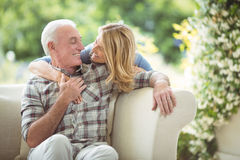 Senior woman embracing a man in living room royalty free stock image