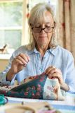 Senior Woman Embroidering Cushion Cover At Home. Senior Woman Embroiders Cushion Cover At Home stock images