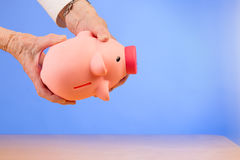 Senior woman empties a piggybank Royalty Free Stock Photography