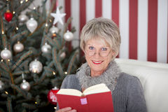 Senior woman enjoying a book at Christmas Royalty Free Stock Images