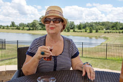 Senior woman enjoying a drink outdoors Royalty Free Stock Photography