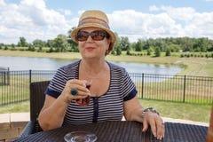 Senior woman enjoying a drink outdoors Royalty Free Stock Photography
