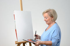 Senior woman enjoying herself painting Royalty Free Stock Images