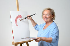 Senior woman enjoying herself painting Stock Photos