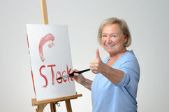 Senior woman enjoying herself painting Stock Images