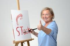 Senior woman enjoying herself painting Stock Images