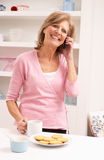 Senior Woman Enjoying Hot Drink Whilst On Phone Royalty Free Stock Image