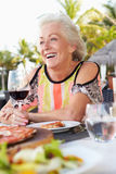 Senior Woman Enjoying Meal In Outdoor Restaurant Royalty Free Stock Images
