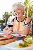 Senior Woman Enjoying Meal In Outdoor Restaurant Stock Images