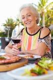 Senior Woman Enjoying Meal In Outdoor Restaurant Stock Images