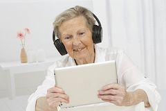 Senior woman enjoying a movie on her tablet device royalty free stock image