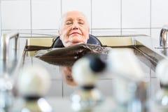 Senior woman enjoying mud bath alternative therapy. In wellness spa royalty free stock image