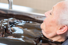 Senior woman enjoying mud bath alternative therapy stock photos