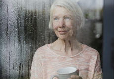 Senior Woman Enjoying The Rain. Senior woman is watching the rain from a window in her home while enjoying a cup of tea Royalty Free Stock Photography