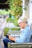 Senior woman enjoying reading book outdoors Stock Photos