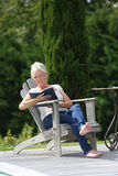 Senior woman enjoying reading outdoors stock image