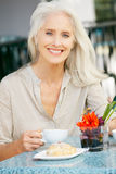 Senior Woman Enjoying Snack At Outdoor Cafe Stock Photo