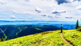 Senior Woman enjoying the view on a hike on Tod Mountain near the alpine village of Sun Peaks in the Shuswap Highlands, BC. Senior Woman enjoying the view on a stock photos