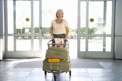 Senior woman entering airport through automatic doors, pushing luggage trolley, smiling, front view, portrait Stock Photos