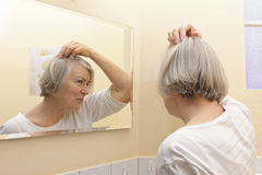 Senior woman examining hair loss. Old woman with thin gray hair and a worried look on her face examining her beginning baldness in the mirror of her yellow royalty free stock photos