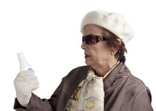 Senior woman examining to a cosmetic bottle Stock Image