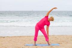 Senior woman exercise. Healthy senior woman exercise on beach Royalty Free Stock Photography