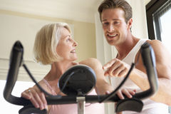 Senior Woman On Exercise Bike With Trainer Stock Image