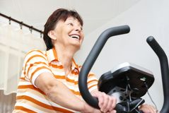 Senior woman exercise at home. Senior (mature) woman exercises on spinning bicycle at home (room interior in background Stock Photos