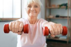 Senior woman exercise at home sitting on exercise ball with dumbbells in front blurred. Senior woman exercise indoors sitting on exercise ball holding dumbbells Royalty Free Stock Image