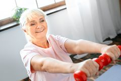 Senior woman exercise at home sitting on exercise ball with dumbbells in front. Senior woman exercise indoors sitting on exercise ball holding dumbbells in front Royalty Free Stock Photo