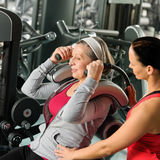 Senior woman exercise with personal trainer. Senior women at gym exercise with personal trainer on machine Royalty Free Stock Images