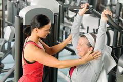 Senior woman exercise on shoulder press machine. Senior women exercise on shoulder press machine with personal trainer royalty free stock photo