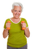 Senior woman exercising. Happy senior woman exercising with two dumbbells Royalty Free Stock Images